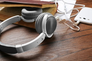 Headphones with old book and smartphone on wooden table